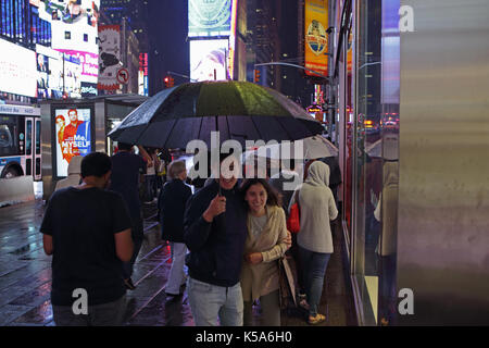 Rainy night in Times Square, tourists with umbrellas walk 7th Avenue and Broadway brightly lit by electric billboard - Stock Photo