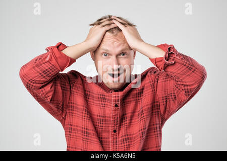 Portrait of young caucasian man in red t-shirt with shocked facial expression, isolated over white background - Stock Photo