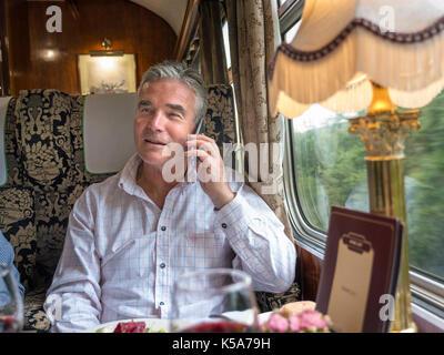 LUXURY First class train carriage & businessman in restaurant rail car talking on smartphone enjoying train trip - Stock Photo