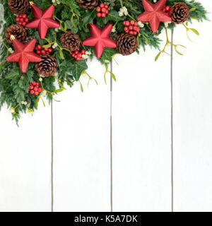 Christmas background border with red stars, holly, fir, ivy, mistletoe and pine cones on distressed white wood. - Stock Photo