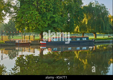 Stratford upon Avon and early morning autumn reflections on the River Avon with a narrow boat moored at the old - Stock Photo