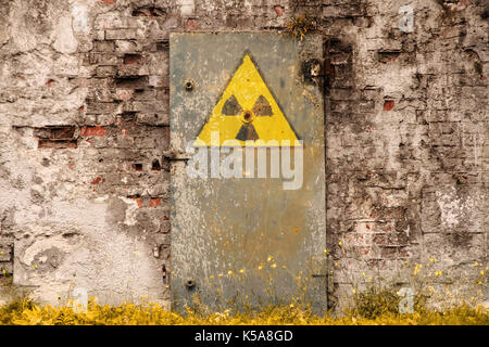 Radioactive (ionizing radiation) danger symbol painted on the old massive rusted iron door of an abandoned structure - Stock Photo