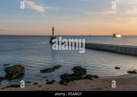 Ferry approaches Aberdeen harbour with oil service ships on the horizon. - Stock Photo
