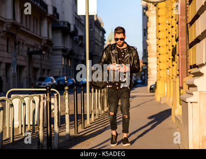 A handsome young hipster man walking on a sunny street while using his smartphone - Stock Photo