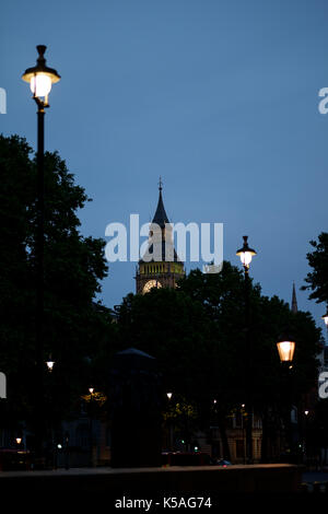London street at dusk with top of Big Ben in background against blue sky - Stock Photo