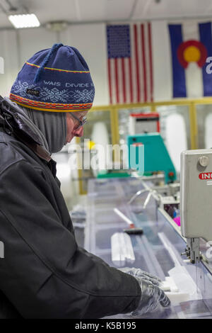 Denver, Colorado - Geoff Hargreaves, curator at the National Ice Core Laboratory, cuts an ice core from Greenland. - Stock Photo
