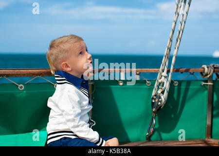 Joyful young captain portrait. Happy child on deck of sailing yacht, have fun discovering islands, travel in tropical - Stock Photo