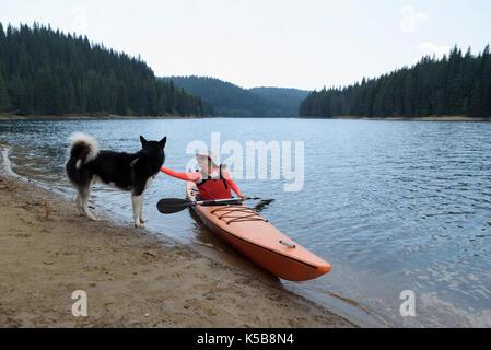 Young woman caress Alaskan Malamute sitting in her kayak - Stock Photo