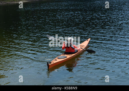 Young woman paddling in alpine lake - Stock Photo