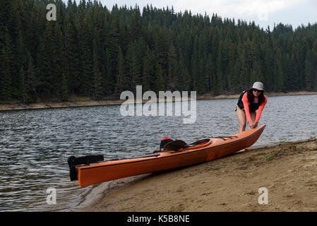 Young woman pulling her kayak on a shore before the rain - Stock Photo