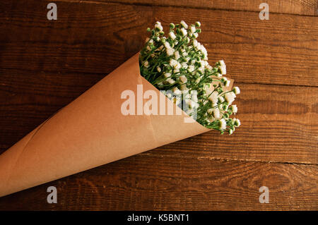 Bouquet of camomile field wrapped in kraft paper on a wooden table - Stock Photo