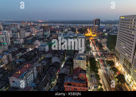 Downtown and lit Sule Pagoda in Yangon, Myanmar, viewed from above in the evening. - Stock Photo