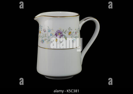 Beutiful floral china milk jug on a black back ground. JUg has two gold bands on the jug one o the main body and - Stock Photo