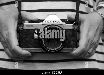 Woman holding vintage Pentax camera - Stock Photo