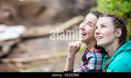 Two young women looking up at something and smiling outdoors - Stock Photo