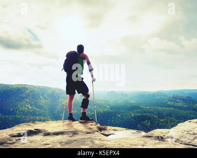 Man with a crutches in nature. Tourist with broken leg on crutches. Traveler with hurt leg in bandages stay on rocky - Stock Photo
