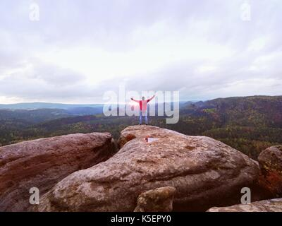 Hiker man stays on a rocky ridge and enjoy view over long valley to horizon. Cold Sun hidden in clouds. National - Stock Photo