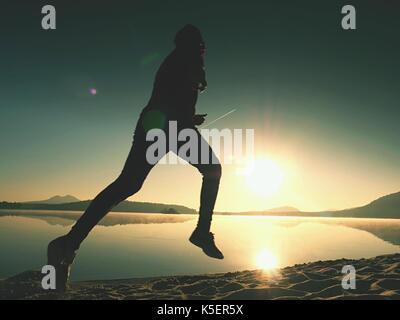 Running man on beach. Sportsman run in baseball cap, jogging guy during the sunrise above sandy beach. Man jumping - Stock Photo