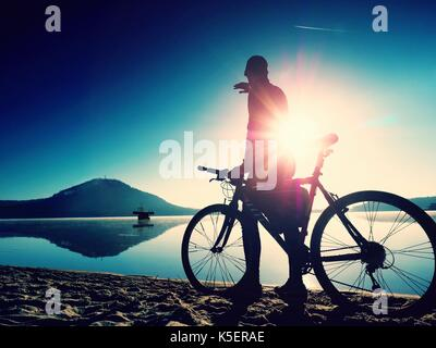 Silhouette of sportsman  holding bicycle on lake beach, colorful  sunset cloudy sky in background and reflection - Stock Photo