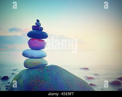 Balance of pebbles against the background of blurred sea.  Smooth atmosphere on hotel beach - Stock Photo
