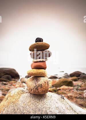 Stones pyramid symbolizing zen, harmony, balance pebbles. Ocean in background. Colorful flat stones for meditation - Stock Photo