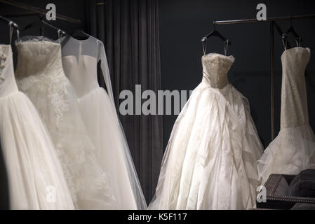 Selection of white wedding dresses or ball gowns on display hanging on rails with selective focus to one illuminated - Stock Photo