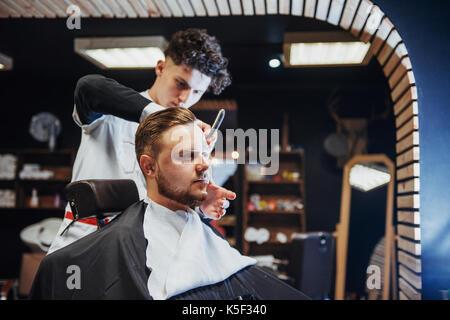 Man hairdresser doing haircut beard adult men in the men's hair salon - Stock Photo