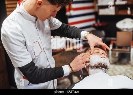 man in the barbershop beard clipper - Stock Photo