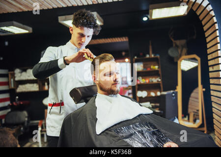 The Barber man in the process of cutting the beard of client electric clippers - Stock Photo