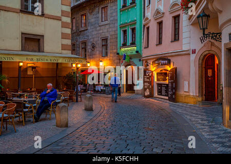 PRAGUE, CZECH REPUBLIC - SEPTEMBER 22, 2015: Small outdoor restaurant on evening cobbled street in Old Town of Prague. - Stock Photo