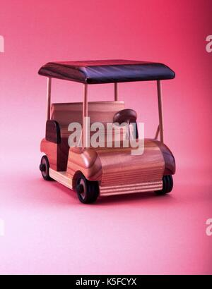 Small wooden toy car on pink background - Stock Photo