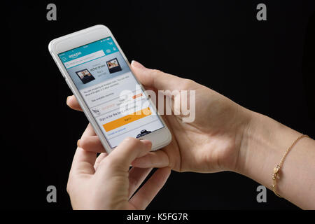 Young woman signing in on AMAZON online service with her mobile - Stock Photo