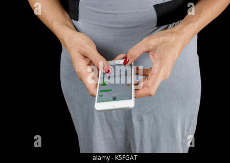 Adult woman in the 40s chatting online with her smartphone. - Stock Photo