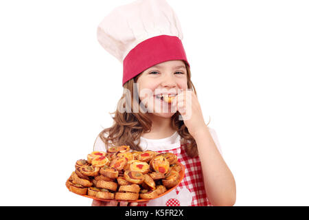 hungry little girl cook eating bruschette - Stock Photo