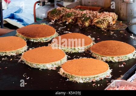 Tokyo, Japan - May 14, 2017: Baking pancakes at a grill, Okonomiyaki, at the Kanda Matsuri Festival - Stock Photo