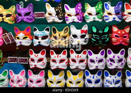 Tokyo, Japan - May 14, 2017:  Cat masks for sale hanging on the wall at the Kanda Matsuri Festival - Stock Photo