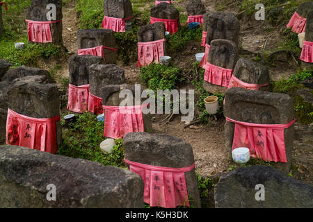 Nara - Japan, May 30, 2017: Peaceful stone relegious Jizo statues with red skirts in the garden - Stock Photo