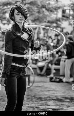 An adolescent girl hula hoops, alone in a crowd, at the drum circle at Pritchard Park in downtown Asheville, NC, - Stock Photo