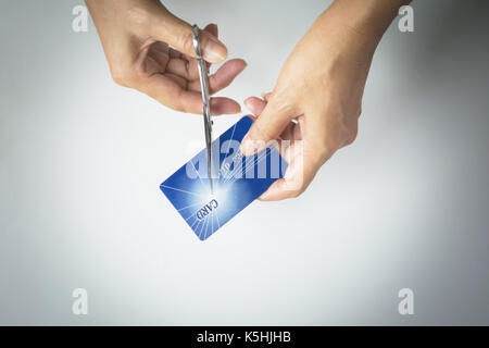 Cutting credit cards with scissors. Female hands cutting credit card with scissors. - Stock Photo