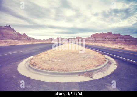 Vintage toned picture of a road in Badlands National Park, travel concept background, South Dakota, USA. - Stock Photo