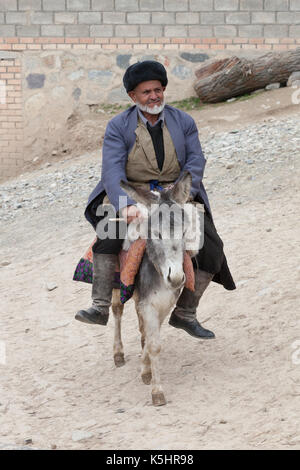 old man riding a donkey in a mountain village - Stock Photo
