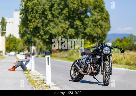 Cool looking motorcycle rider sitting near custom made scrambler style cafe racer - Stock Photo