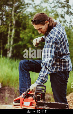 The logger in a red checkered shirt is holding an chainsaw is going to start it, against the forest - Stock Photo