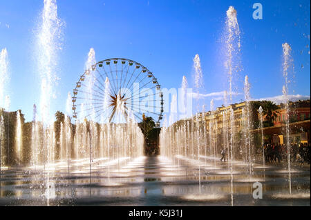 View of the water jets in the city of Nice (French Riviera) during Christmas holidays.The Ferris wheel is in the - Stock Photo