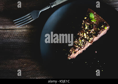 Dark chocolate cheesecake decorated with chopped pistachios and mint leaf on black plate on wooden table. Top view, - Stock Photo