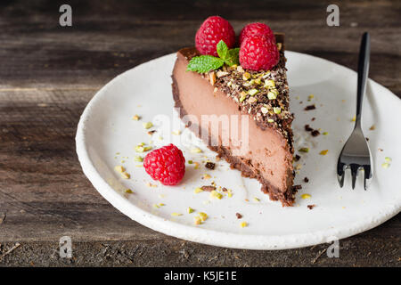 Slice of chocolate cheesecake decorated with pistachios, raspberries and mint leaf on white plate on wooden background. - Stock Photo