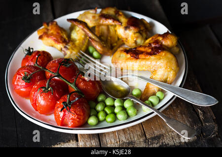 Spicy chicken wings, roasted cherry tomatoes and sauteed green peas on white plate. Baslanced meal. Closeup view, - Stock Photo