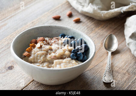 Oatmeal porridge with blueberries, almonds, linseeds in bowl on wooden table. Super food for healthy nutritious - Stock Photo