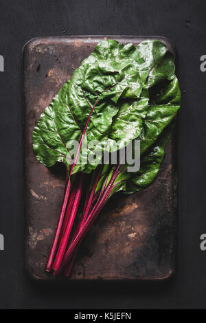 Fresh swiss chard leaves on dark rusty background. Table top view fresh organic green food - Stock Photo
