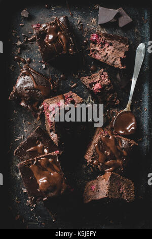 Chocolate cherry brownies decorated with melted chocolate on dark background. Table top view - Stock Photo